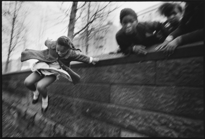 Girl jumping over a wall by Mary Ellen Mark