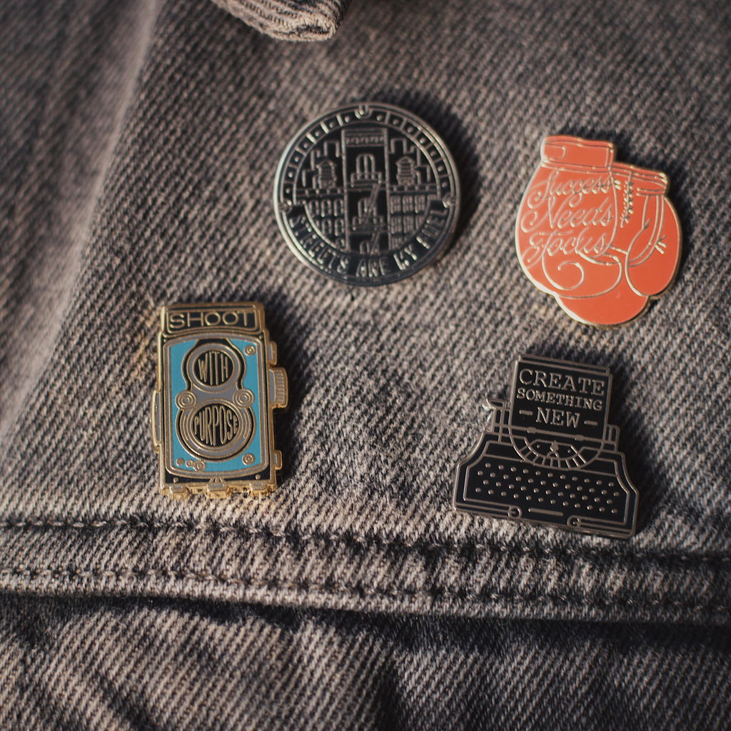 Four enamel pins on a denim jacket by Reghan Skerry
