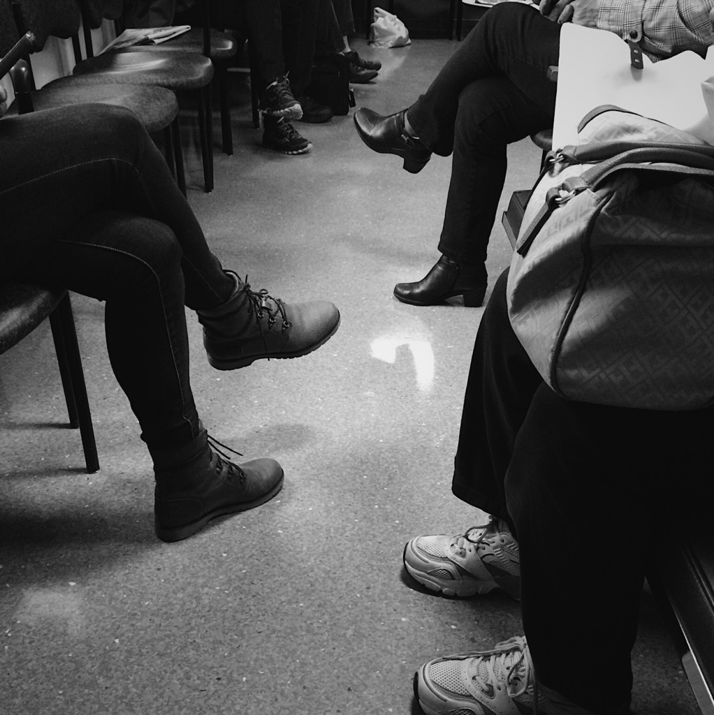 Black and white photo of people in a waiting room (shoes only) by Reghan Skerry