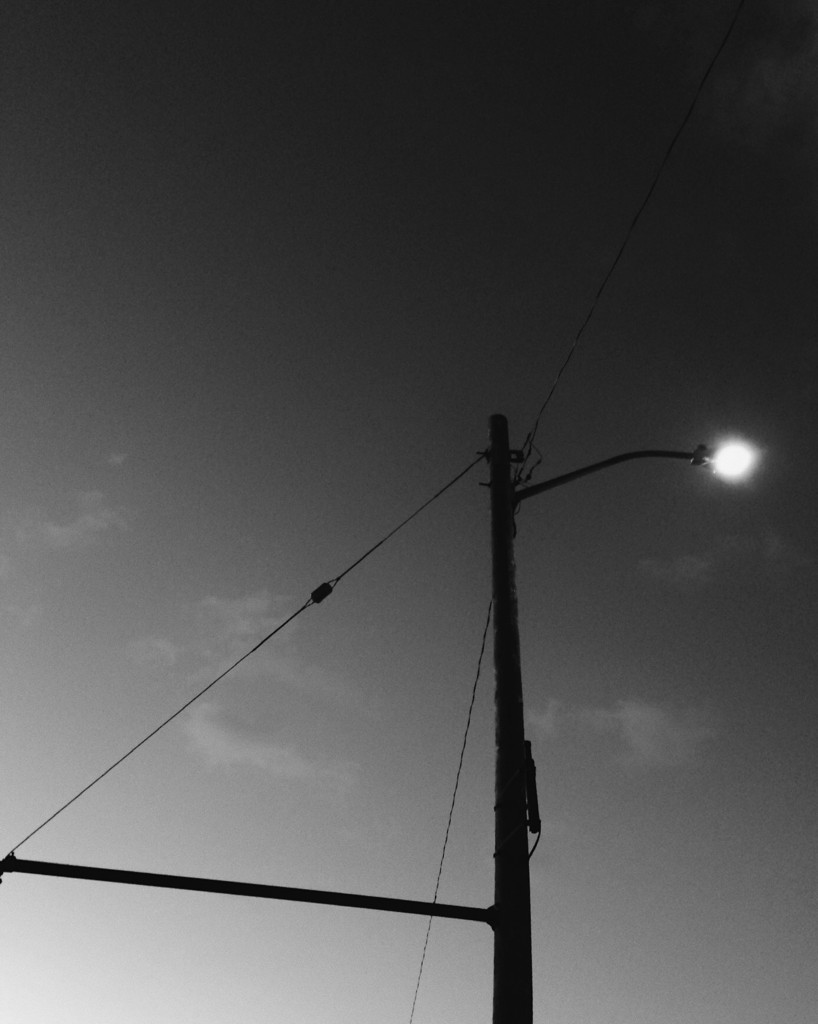 Black and white photo of a lamppost in dawn light by Reghan Skerry