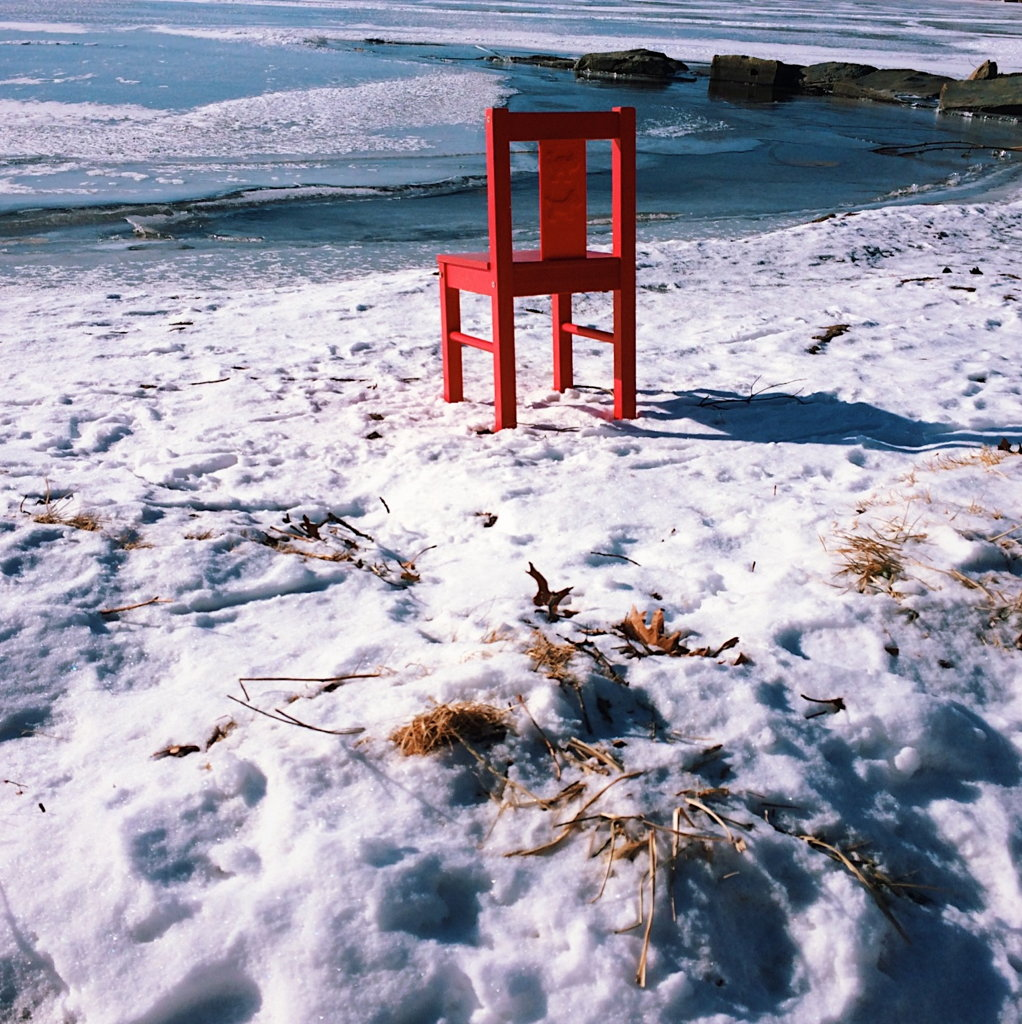Photo of a red chair next to a frozen lake by Reghan Skerry