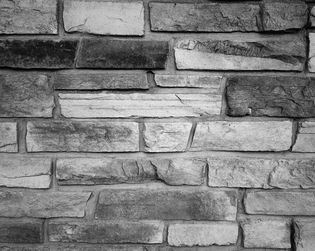 Black and white photo of a stone wall by Reghan Skerry