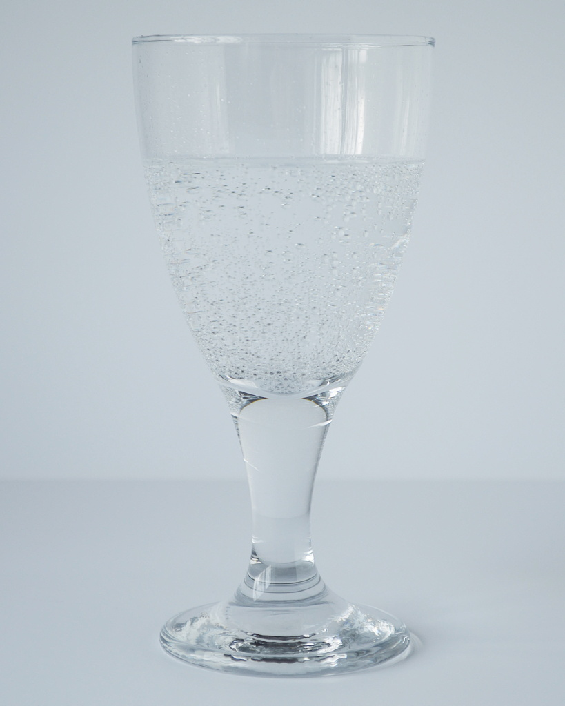 Photo of a wine glass filled with sparkling water, against a white backdrop, by Reghan Skerry