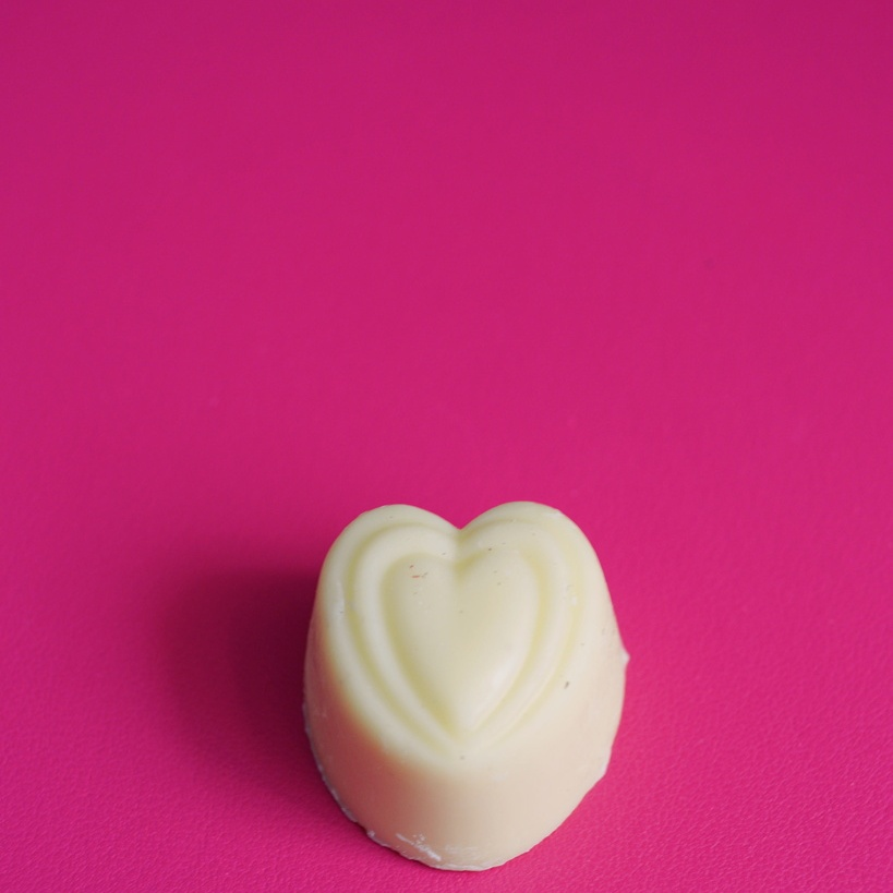 Heart-shaped white chocolate candy on a bright pink background, photographed by Reghan Skerry