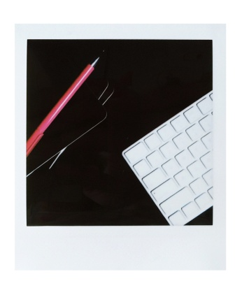 Instax square photo of a keyboard, black notebooks, and a pink pen, photographed by Reghan Skerry.