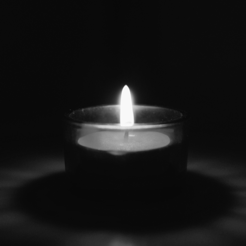 Black and white photo of a burning tealight, photographed by Reghan Skerry.