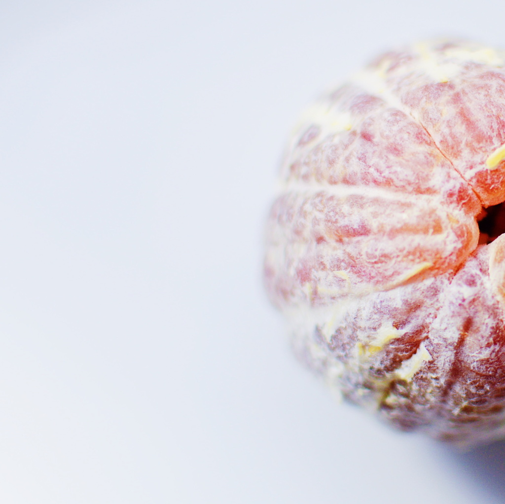 Close up of a peeled blood orange on a white background. Photo by Reghan Skerry.