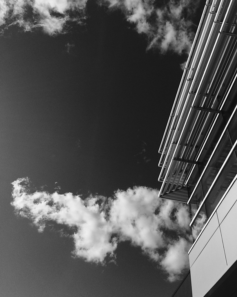 Black and white photo of the corner of a modern building, with clouds in the sky. Photo by Reghan Skerry.