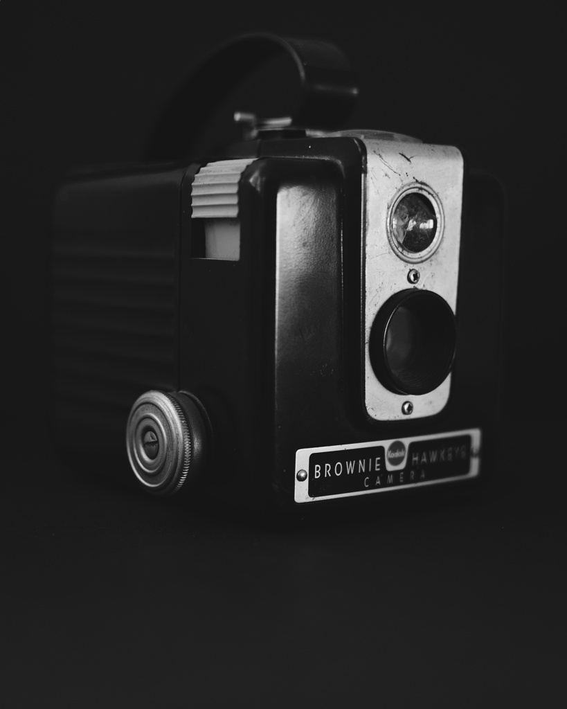 Dark black and white photo of a Kodak Brownie Hawkeye camera. Photo by Reghan Skerry.
