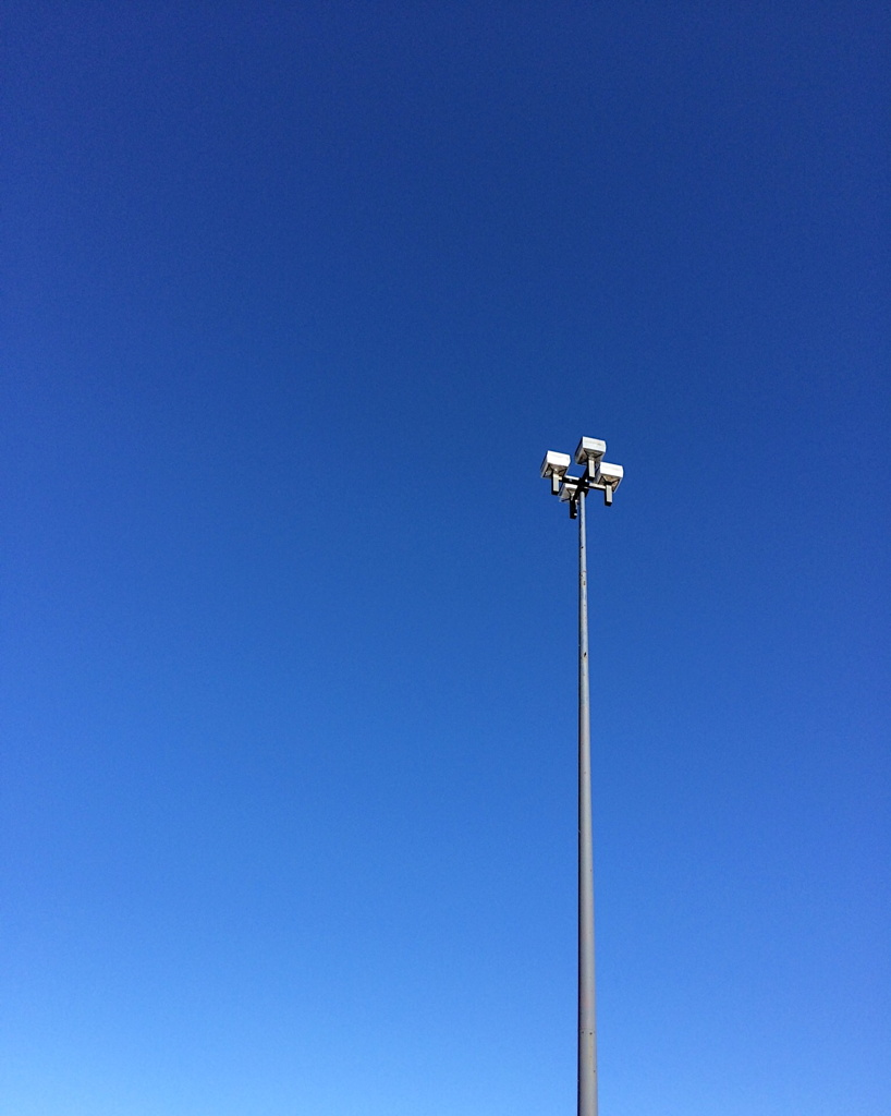Lamp post against a cloudless blue sky. Photo by Reghan Skerry.