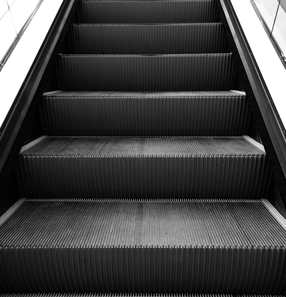 Black and white photo of an escalator, by Reghan Skerry.