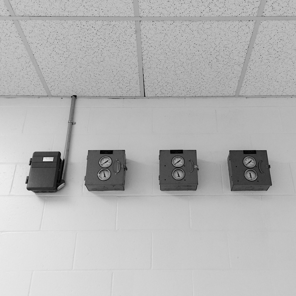 Black and white photo meters on a cinderblock wall, by Reghan Skerry.