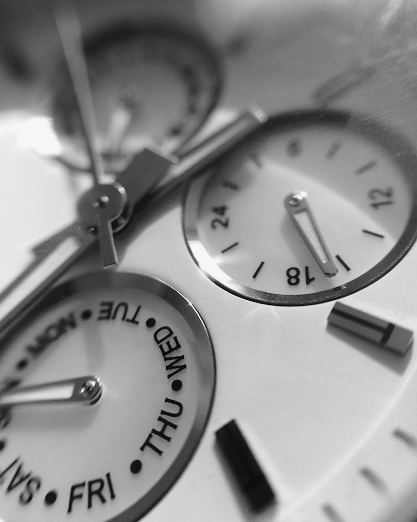 Black and white close-up of a watch face. Photo by Reghan Skerry.