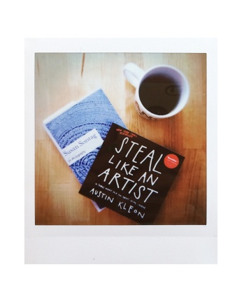 Instax square photo of Steal Like an Artist by Austin Kleon and On Photography by Susan Sontag, and a cup of coffee. Photo by Reghan Skerry.