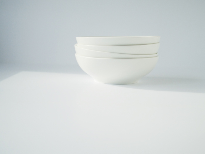 A stack of white bowls against a white background. Photo by Reghan Skerry.
