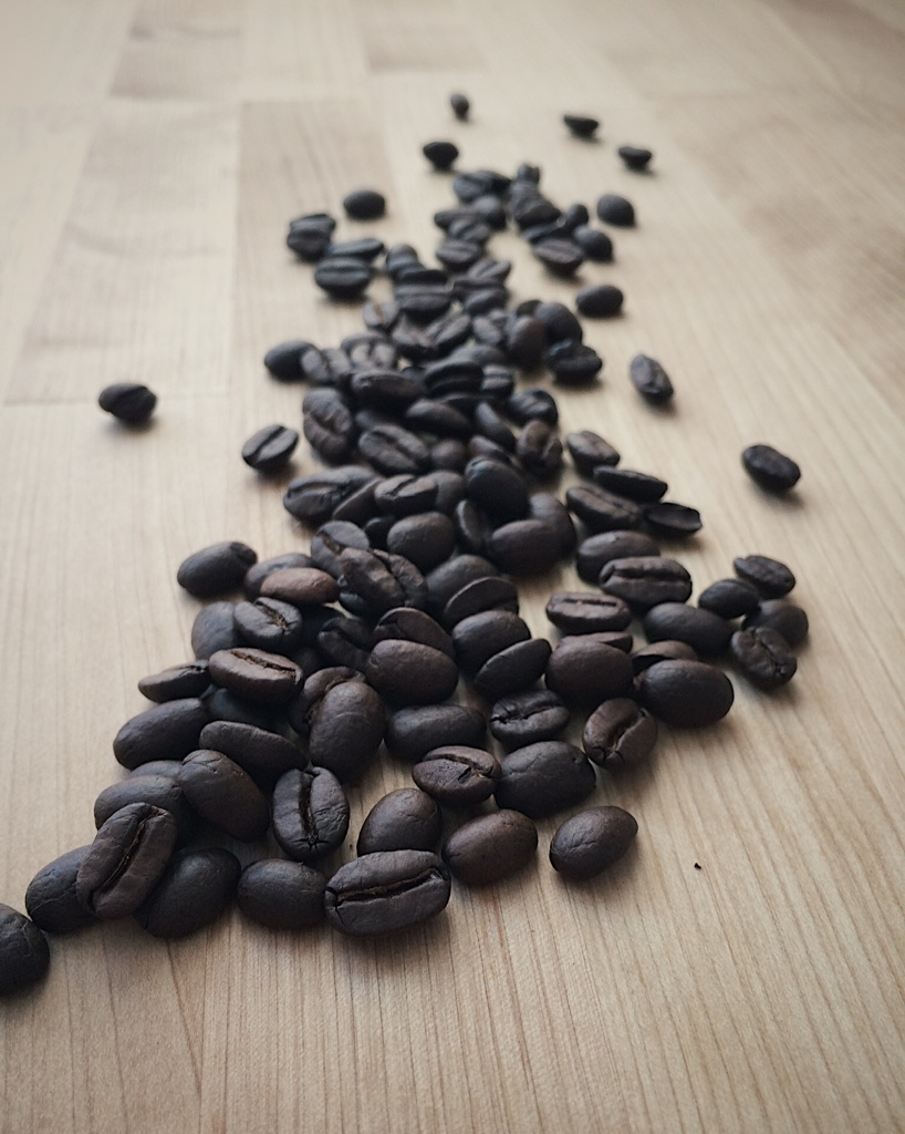 Coffee beans spilled on a butcher block. Photo by Reghan Skerry.