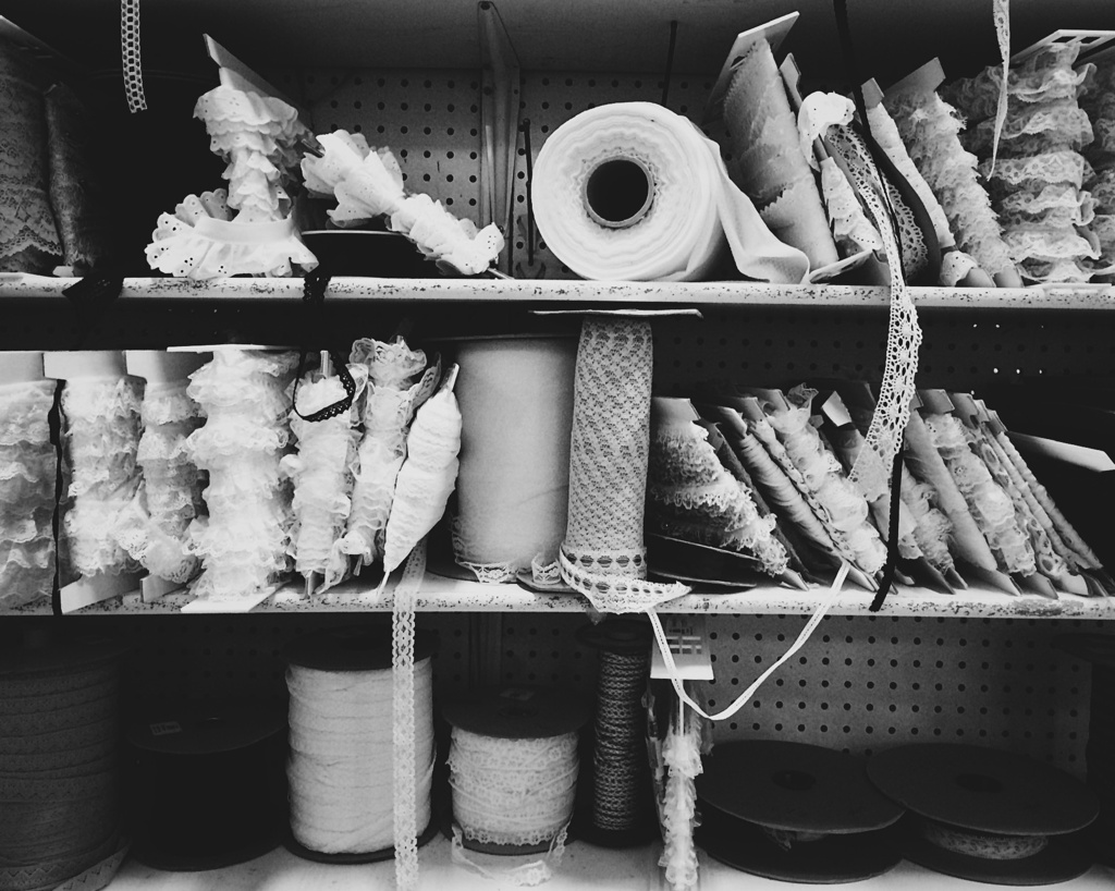 Black and white photo of spools of lace on a shelf. Photo by Reghan Skerry.
