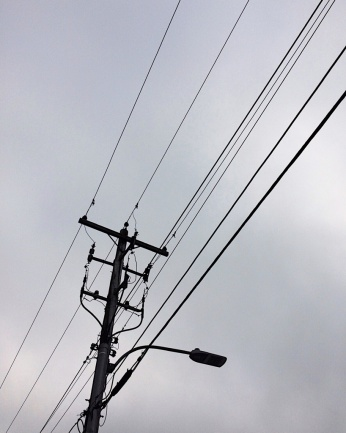 Lamp post with wires, against a grey sky. Photo by Reghan Skerry.
