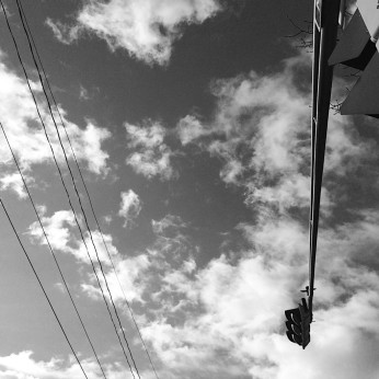 Black and white photo of streetlights against clouds. Photo by Reghan Skerry