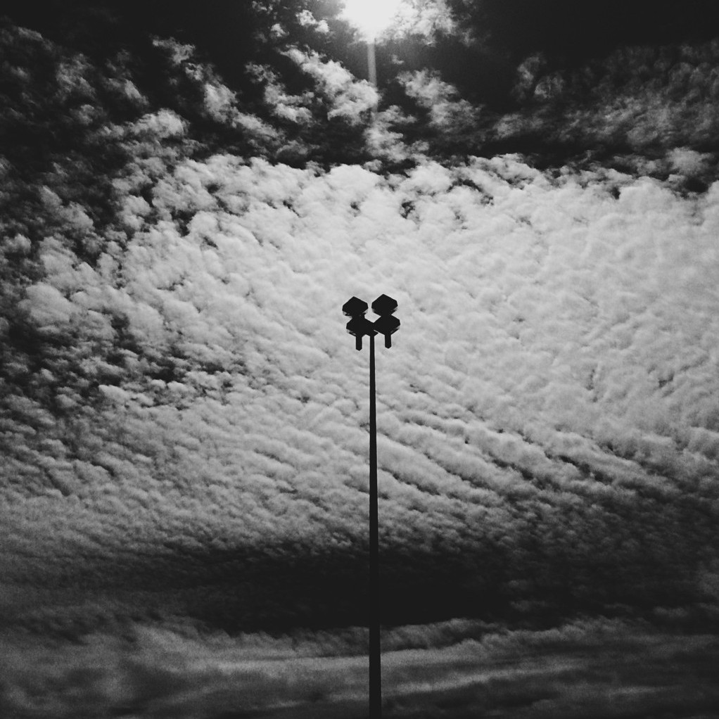 Black and white photo of a lamp post silhouetted against dramatic clouds. Photo by Reghan Skerry