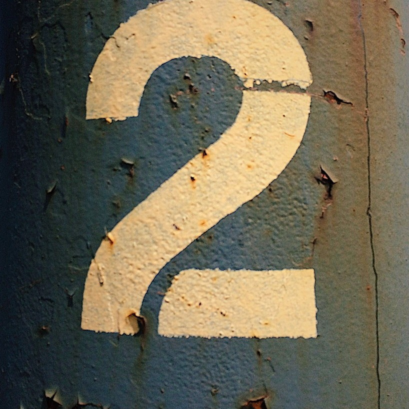 Stencilled number 2 on a rusting metal surface. Photo by Reghan Skerry.