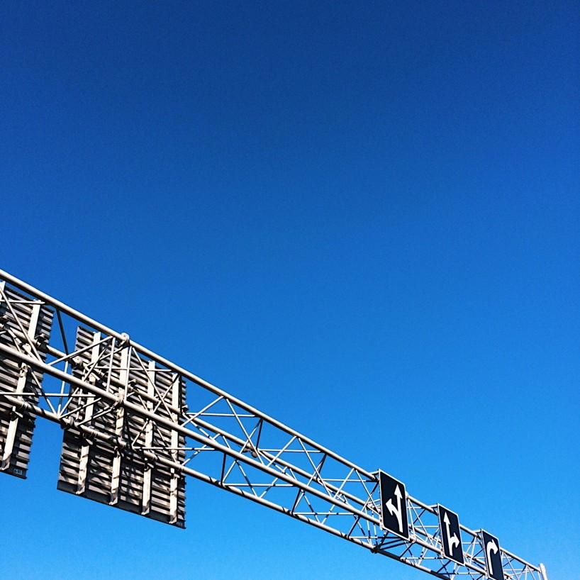 Highway sign against a cloudless blue sky. Photo by Reghan Skerry.