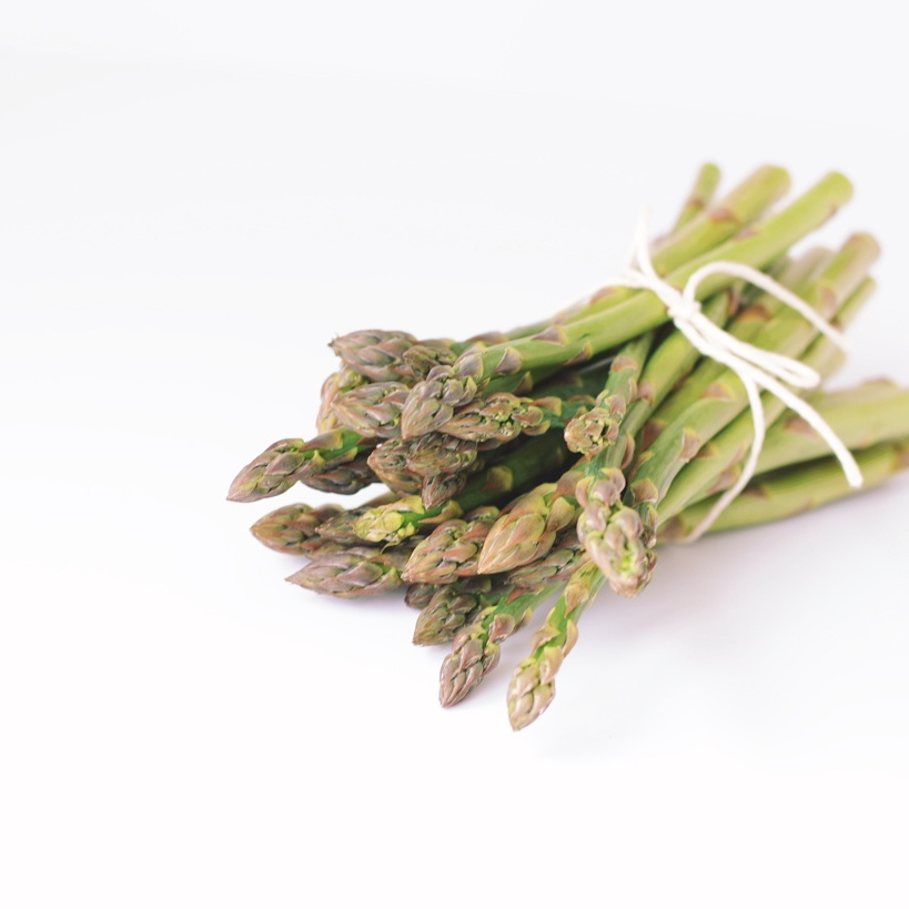 Asparagus stalks bundled with string, against a white background. Photo by Reghan Skerry.