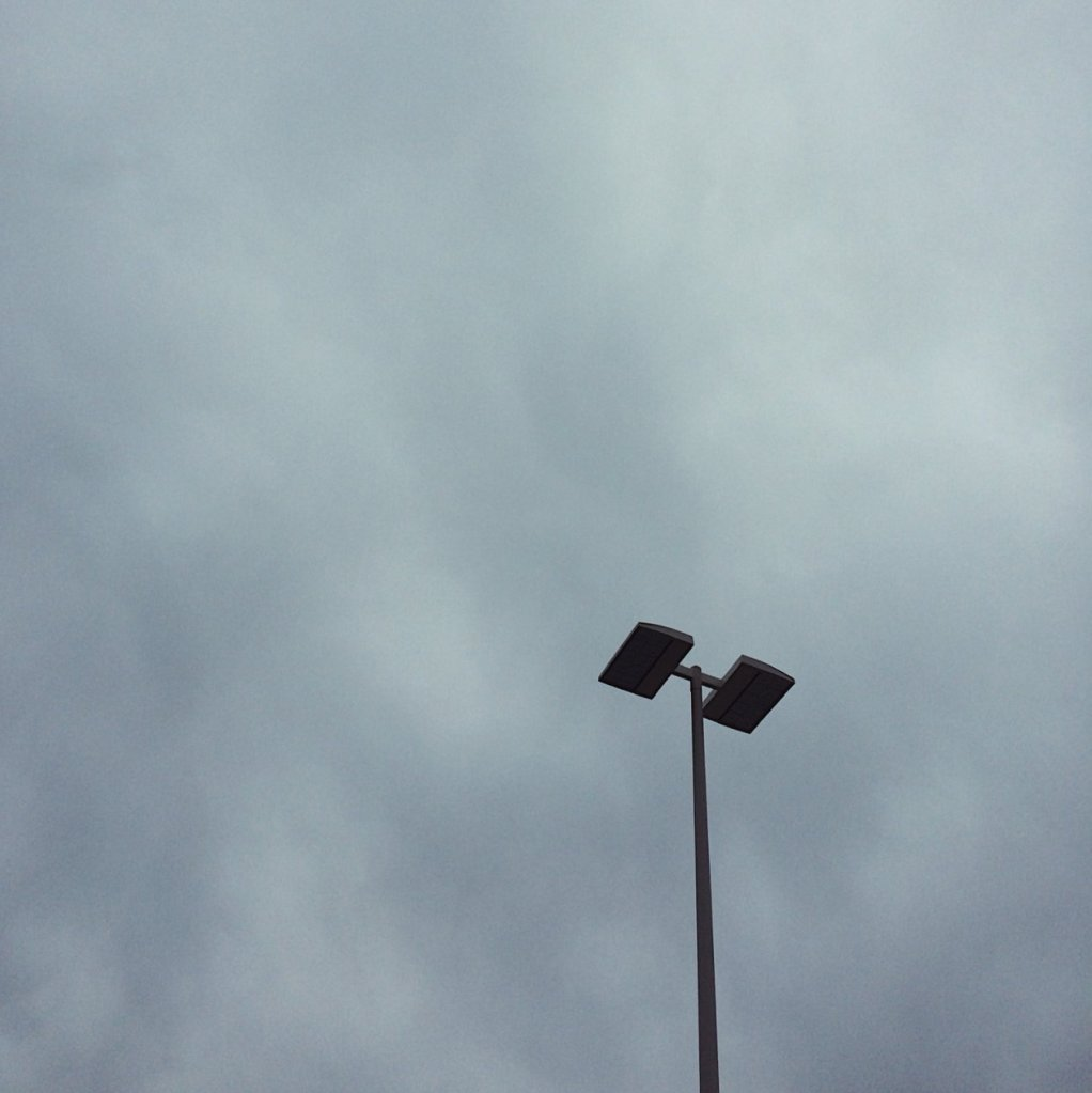 Lamp post against a cloudy sky. Photo by Reghan Skerry.