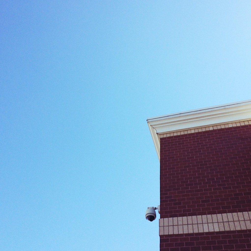 Corner of a brick building with a security camera. Photo by Reghan Skerry.