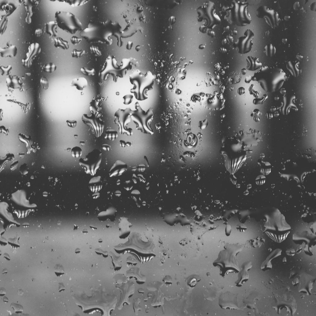 Black and white photo of raindrops on a window. Photo by Reghan Skerry.