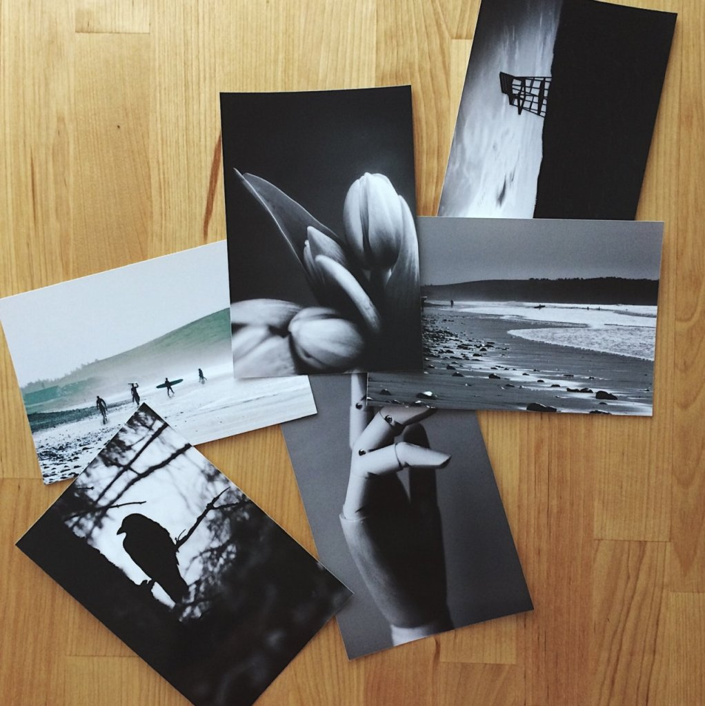 Prints of photos on a wooden table. Photo by Reghan Skerry.