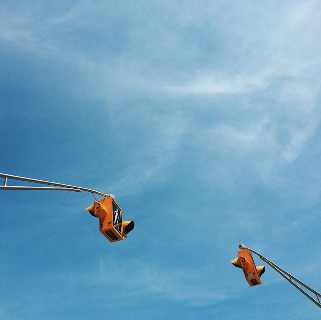 Crosswalk signs in front of a blue sky. Photo by Reghan Skerry.