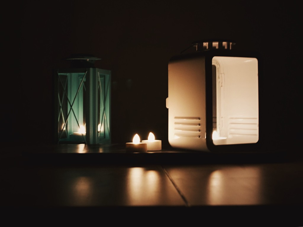 Lanterns and candles in a dark room. Photo by Reghan Skerry.