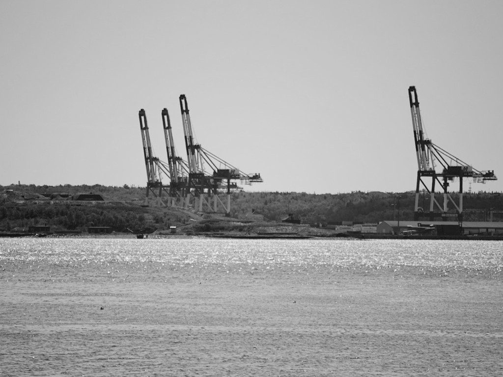 Black and white photo of four industrial cranes across Halifax Harbour. Photograph by Reghan Skerry.