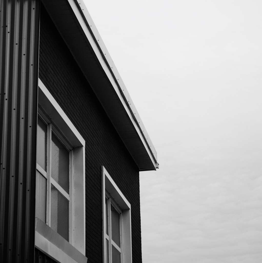 Black and white photo of a dark building with white-framed windows. Photo by Reghan Skerry.