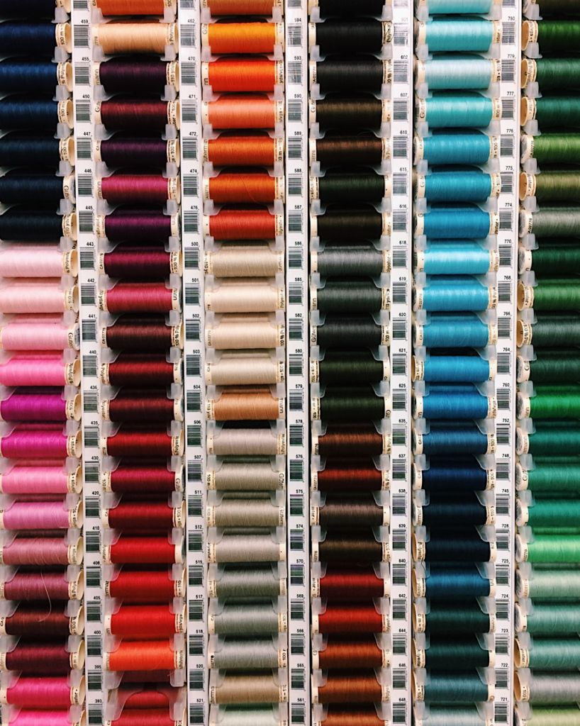 Spools of thread arranged by colour. Photo by Reghan Skerry.