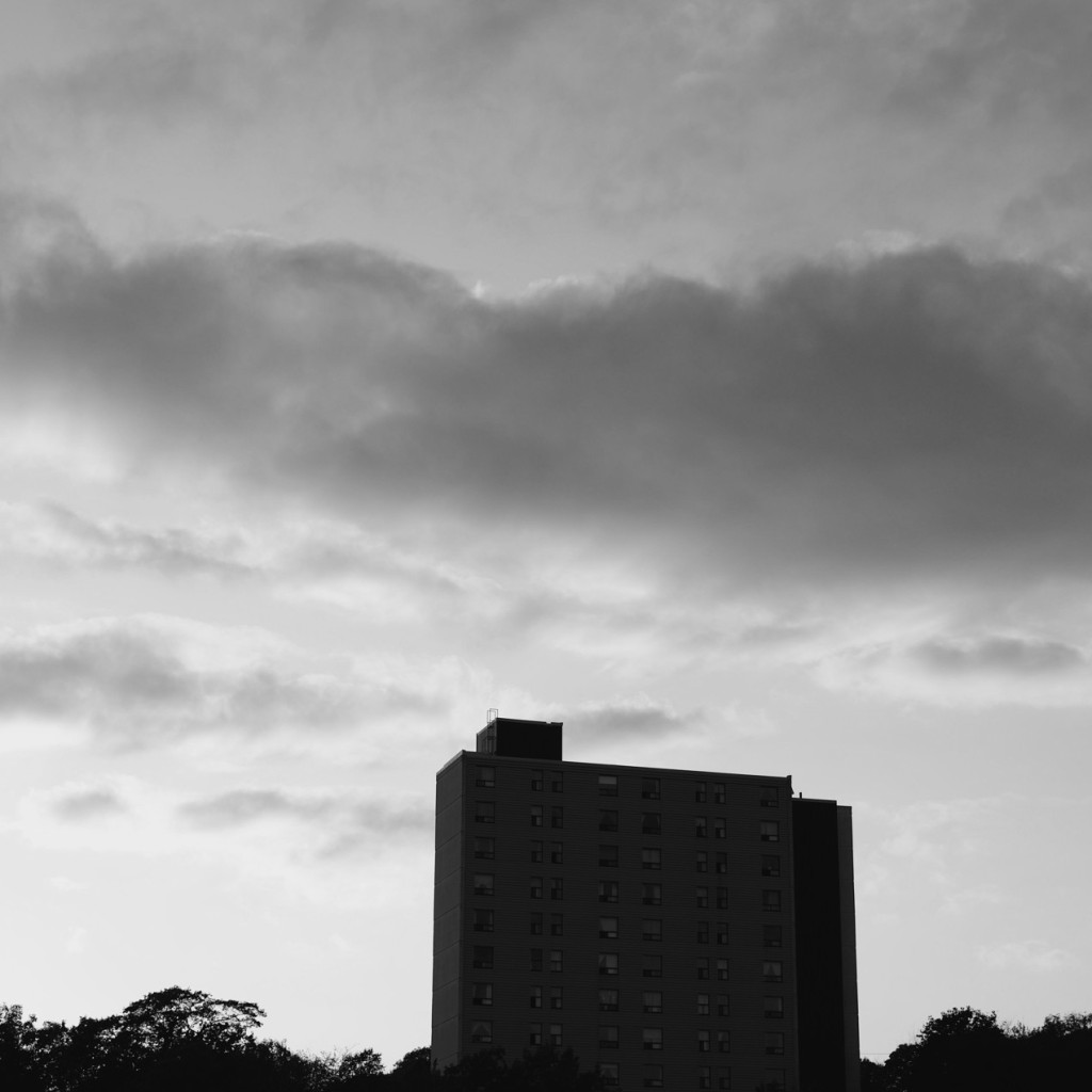 Silhouette of an apartment building against a cloudy sky. Black and white photo by Reghan Skerry.