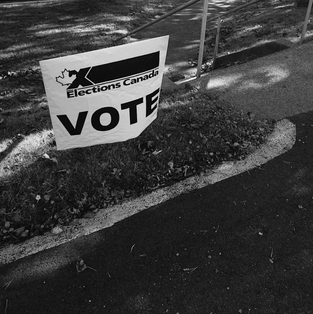 Black and white photo of an Elections Canada 'VOTE' sign. Photo by Reghan Skerry.