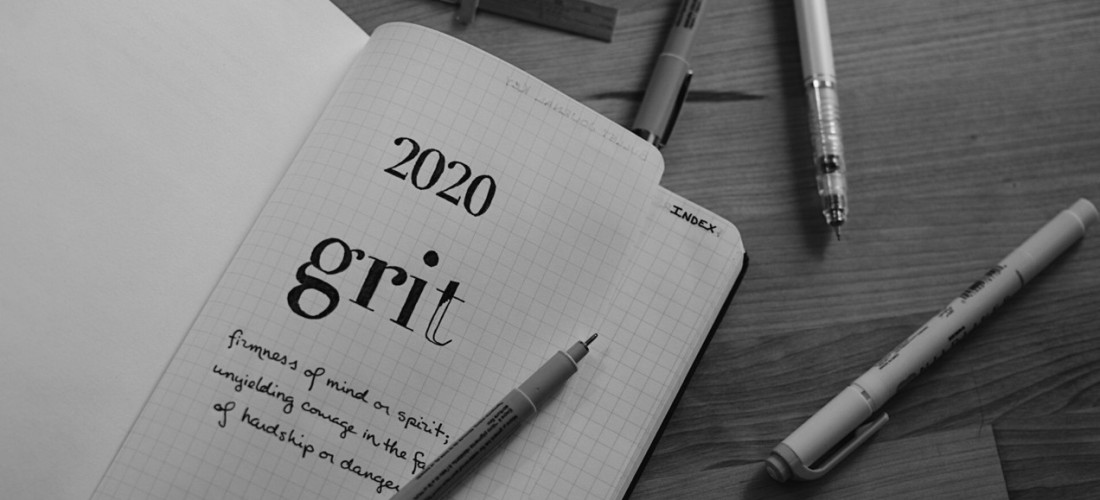 Black and white photo of an open notebook with the year '2020' and word 'grit' written on the first page. Photo by Reghan Skerry.