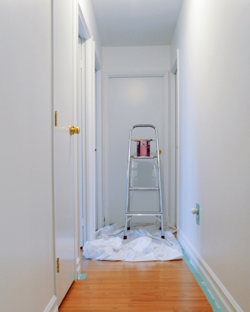 Narrow hallway with a ladder and can of paint. Photo by Reghan Skerry.