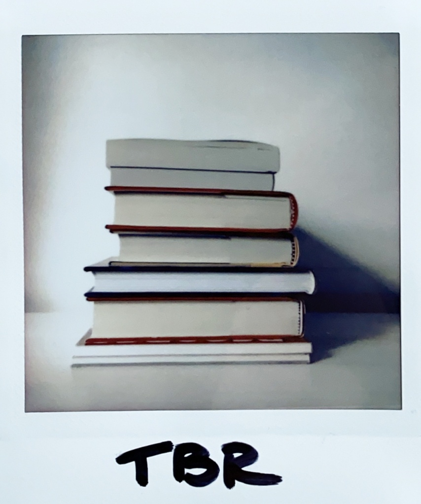 Instax photo of a stack of books, labelled 'TBR.' Photo by Reghan Skerry.