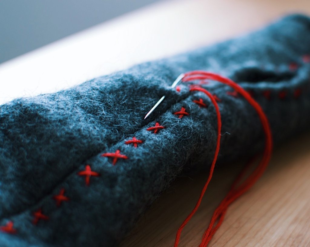 Red embroidery on grey felt. Photo by Reghan Skerry.