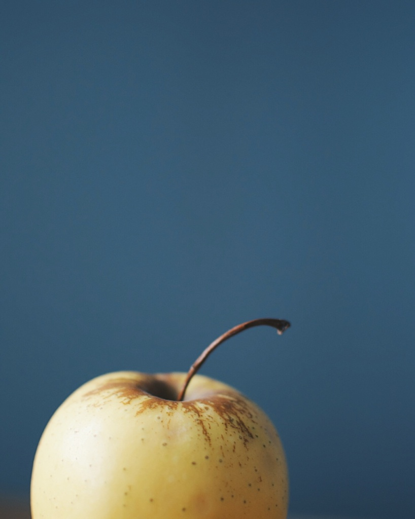 Yellow apple against a blue-grey backdrop. Photo by Reghan Skerry.