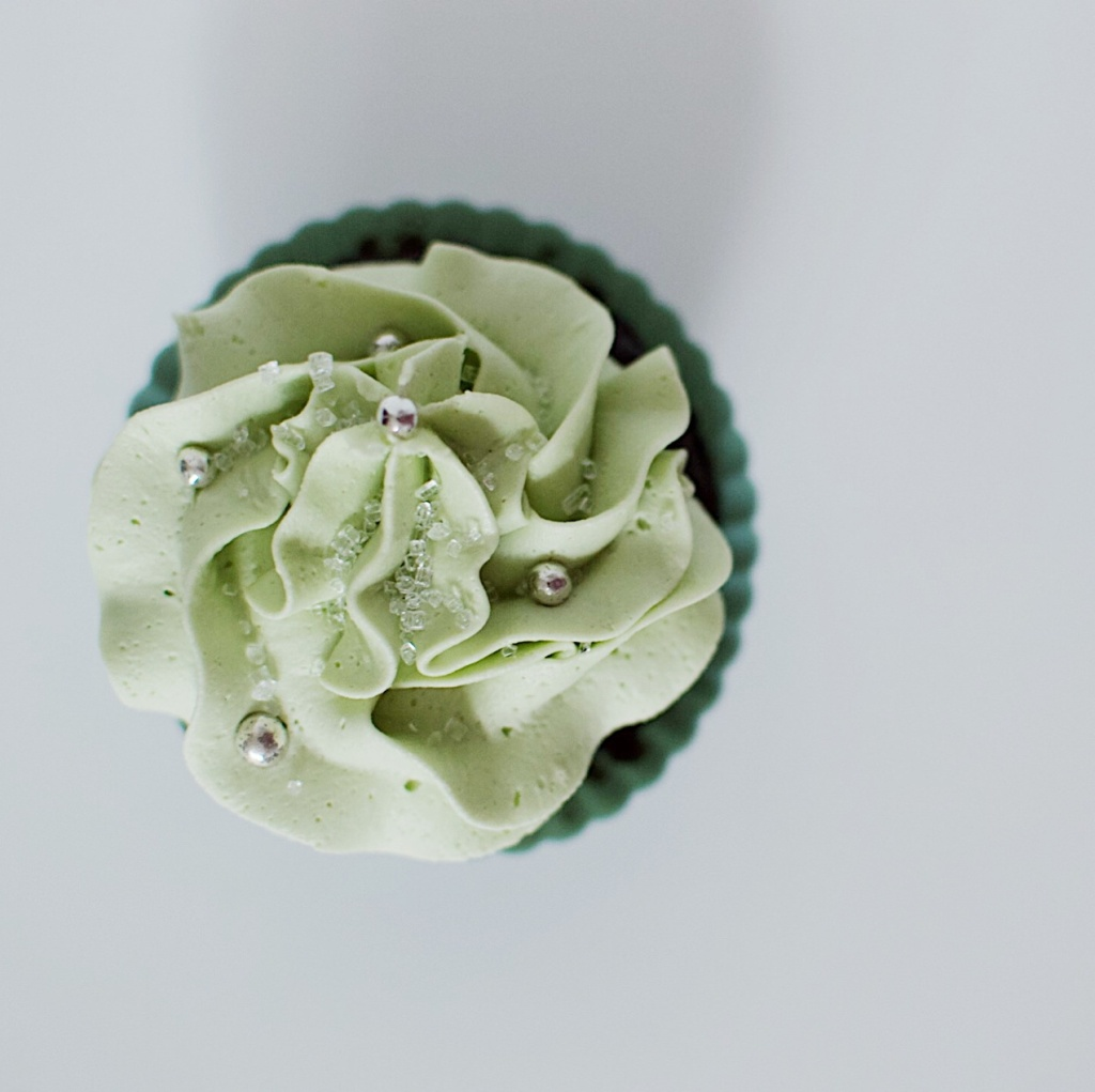 Top-down view of a cupcake with green frosting and silver sprinkles. Photo by Reghan Skerry.