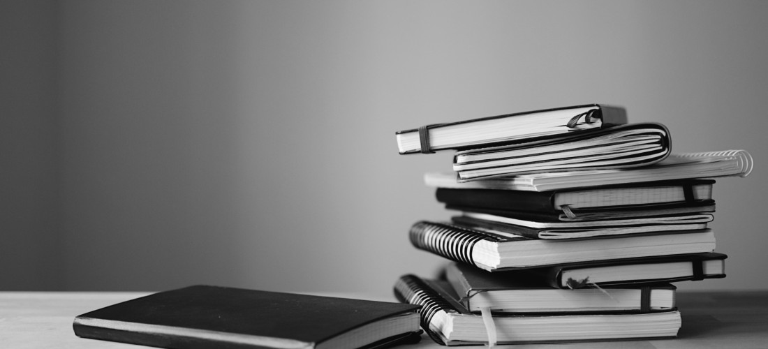 A stack of notebooks and sketchbooks in black and white. Photo by Reghan Skerry.