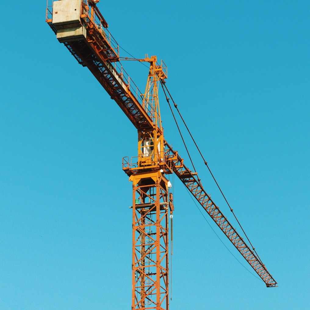 Yellow construction crane against a blue sky. Photo by Reghan Skerry.