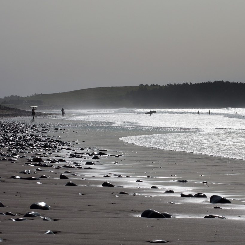 Surfers on a misty beach. Photo by Reghan Skerry.