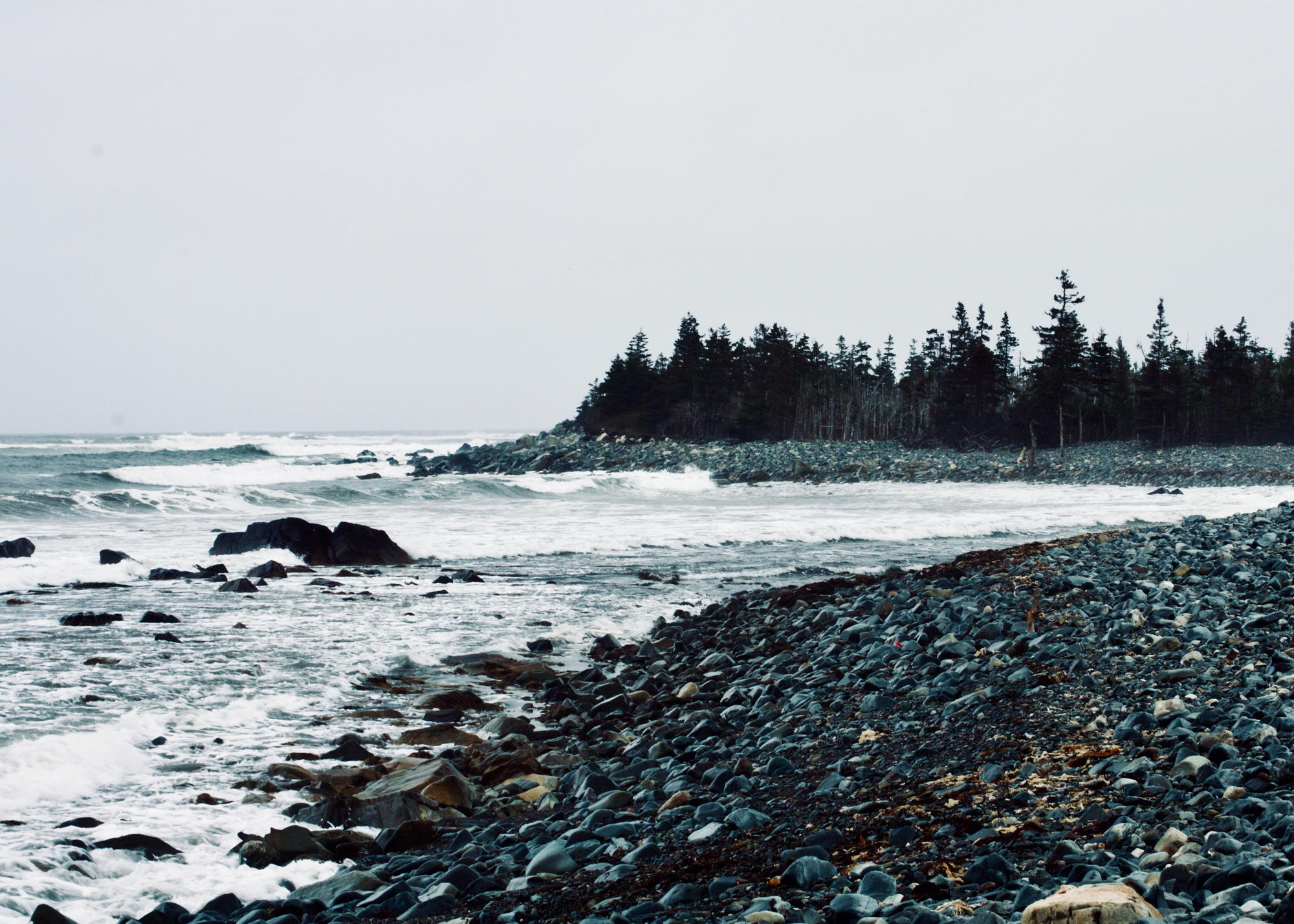 A rocky beach on a cloudy day, with waves crashing into a rocky outcropping. Photo by Reghan Skerry